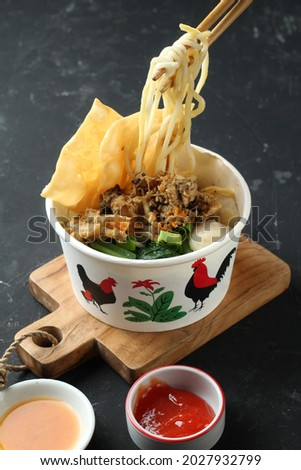 Mie ayam is a popular food in Indonesia, made from noodles topped with stir-fried chicken, green mustard, meatballs, fried dumplings, served with sauce and chili sauce Zdjęcia stock ©