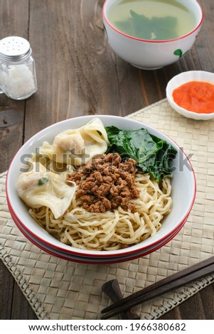 Mie Ayam Pangsit (Noodles with Chicken, Dumplings and vegetables ) is Indonesian popular food. Served in bowl on wooden table. Selective focus. Zdjęcia stock ©