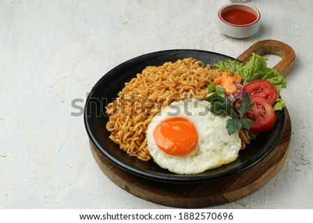 Mie goreng or Fried noodles served with eggs and vegetables, on a plate Zdjęcia stock ©