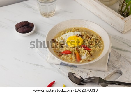 Mie Kuah Telur for Sahur in Ramadan, Instant noodle soup  served on white bowl with boiled pouch egg and chili.  White marble background. Copy space for text.  Zdjęcia stock ©