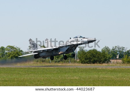 MiG 29 with digital camouflage taking off against clear sky