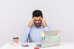 Migraine of stressful job. Depressed man employee sitting in office, clasping head temples, suffering headache and tension, worried about problems at work. studio shot isolated on white background