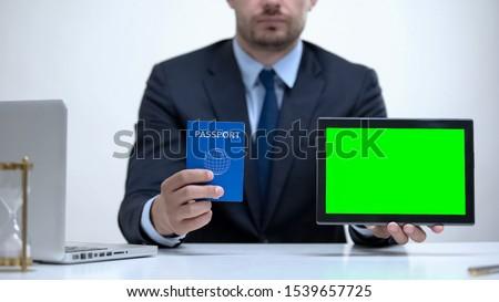 Migration agent holding passport and tablet, tourist visa application online