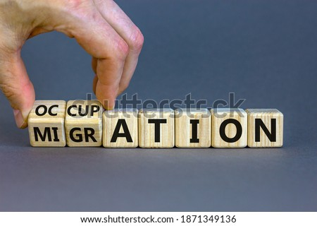 Migration or occupation symbol. Male hand turns cubes and changes the word 'migration' to 'occupation'. Beautiful grey background. Business and migration or occupation concept. Copy space. Stock photo ©
