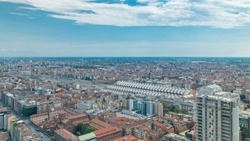 Milan aerial view of residential buildings and the central railway station in the business district timelapse fiew from rooftop. Houses with red roofs. Blue cloudy sky at summer day