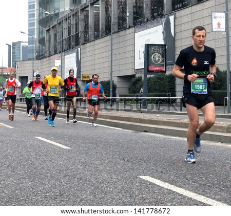 MILAN - APRIL 07: A runner leading a group of athletes during the competition on the city streets at Milano City Marathon on April 07, 2013 in Milan, Italy.