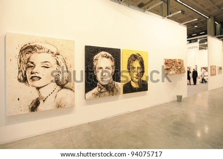 MILAN - APRIL 08: Looking at paintings dedicated to Marilyn Monroe, Paul Newman and John Lennon at MiArt, international exhibition of modern and contemporary art on April 08, 2011 in Milan, Italy. - stock photo