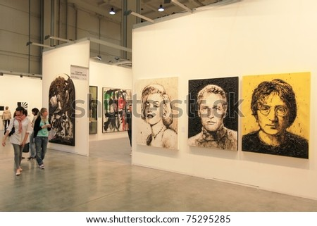 MILAN - APRIL 08: People look at paintings dedicated to Marilyn Monroe, Paul Newman and John Lennon at MiArt, international exhibition of modern and contemporary art on  April 08, 2011 in Milan, Italytthanks