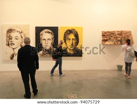 MILAN - APRIL 08: People look at paintings dedicated to Marilyn Monroe, Paul Newman and John Lennon at MiArt, international exhibition of modern and contemporary art on April 08, 2011 in Milan, Italy.