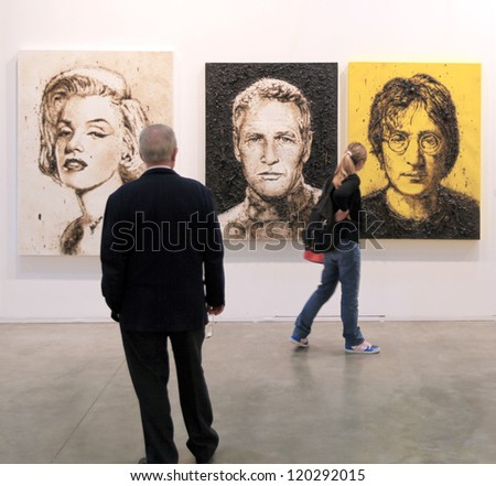 MILAN APRIL 08 People look at paintings galleries during MiArt international exhibition of modern and contemporary art on April 08 2011 in Milan Italy