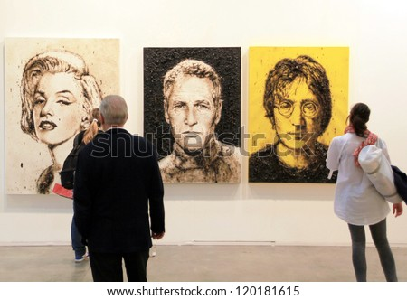 MILAN - APRIL 08: People look at paintings representing Monroe, Newmann and Lennon during MiArt, international exhibition of modern and contemporary art on April 08, 2011 in Milan, Italy