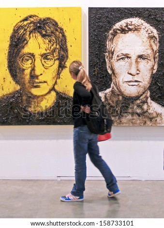 MILAN - APRIL 08: Woman look at paintings galleries during MiArt, international exhibition of modern and contemporary art on April 08, 2011 in Milan, Italy
