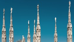 Milan Cathedral roof, Italy. Famous Milan Cathedral or Duomo di Milano is a top landmark of Milan. Many luxury spires with statues on blue sky background. Beautiful Gothic architecture of Milan city.