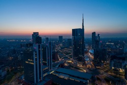 Milan city skyline at dawn, aerial view, flying over financial area skyscrapers in Porta Nuova district.