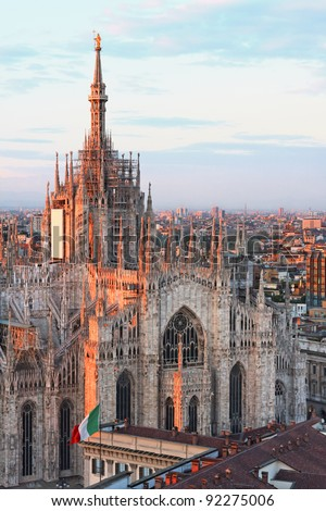 Milan gothic cathedral at dusk as seen by Martini's terrace with the italian flag pictured too
