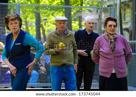 MILAN ITALY APRIL 12 Elderly man and women playing bocce together in an outdoor park in Milan April 12 2011