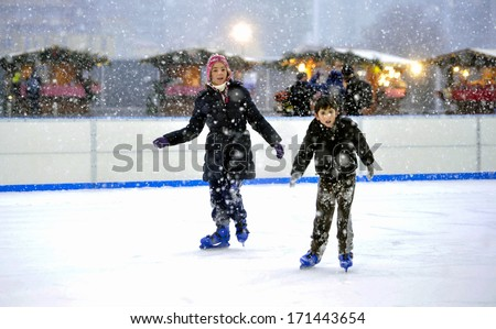 MILAN, ITALY - FEBRUARY 07: a boy and a  girl ice skating in an outdoor public ice skating ring under a snowfall in Milan. February 07, 2009.