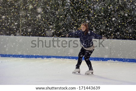 MILAN, ITALY - FEBRUARY 07: a girl ice skating in an outdoor public ice skating ring under a snowfall in Milan. February 07, 2009.