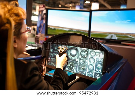 MILAN, ITALY - FEBRUARY 17: A visitor plays on a flight simulator at BIT International Tourism Exchange on february 17, 2012 in Milan, Italy.