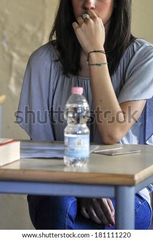MILAN, ITALY-JUNE 20, 2012: College student seat on school desk in the exam room, for the secondary school\'s final exams, at the Artemisia Gentileschi School in Milan.