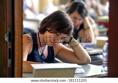 MILAN, ITALY-JUNE 20, 2012: College students seat on school desk in the exam room, for the secondary school\'s final exams, at the Artemisia Gentileschi School in Milan.