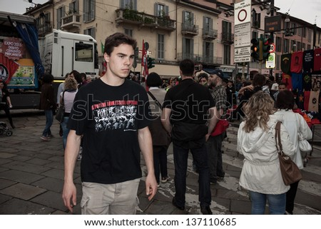 MILAN, ITALY - MAY 1: May Day parade in Milan MAY 1, 2013. A young man with people march in the streets for the traditional celebration of the May Day with an always participated parade
