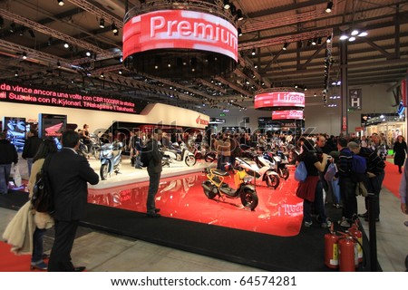 MILAN, ITALY - NOV. 03: People trough stands at EICMA, 68th International Motorcycle Exhibition November 03, 2010 in Milan, Italy.