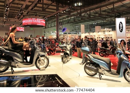 MILAN, ITALY - NOV. 03: People visit Honda motorcycles stand in exhibition at EICMA, 68th International Motorcycle Exhibition November 03, 2010 in Milan, Italy.