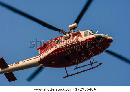 MILAN, ITALY - OCTOBER 13: Fire fighter rescue helicopter flying, with a blue sky in the background, in Milan October 13, 2005.