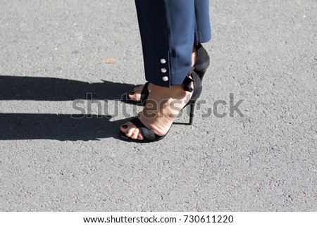 Milan, Italy - September 22, 2017: Model wearing a pair of black shoes with the heel during the Armani parade, photographed in the street #730611220
