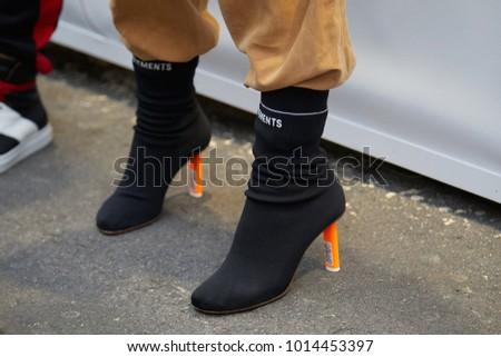 MILAN - JANUARY 15: Woman with black Vetements boots with orange heel and beige suede trousers before Represent fashion show, Milan Fashion Week street style on January 15, 2018 in Milan. #1014453397