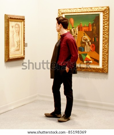 MILAN - MARCH 27: A man looks at a painting of arts galleries during MiArt ArtNow, international exhibition of modern and contemporary art March 27, 2010 in Milan, Italy.