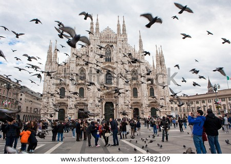 MILAN - NOV 3: Tourists visit the largest cathedral in Italy, Duomo di Milano while a flock of pigeons flies overhead surprisingly on Nov 3, 2012 in Milan.The Cathedral is a main landmark of the city.