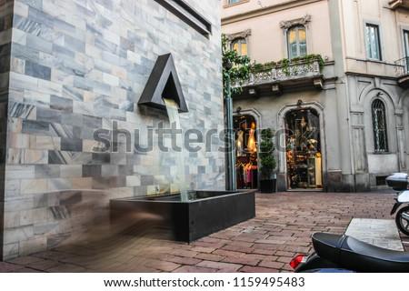Milan Pertini Monument Fountain in via Montenapoleone with Shop. Long Exposure