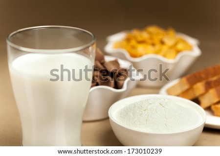 Mild, toast, cornflakes and milk powder on breakfast table