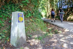 Milestone of Saint James way with unrecognizables pilgrims walking in the background