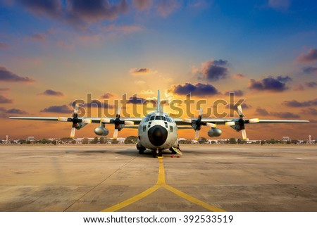 Military aircraft on the runway during sunset.