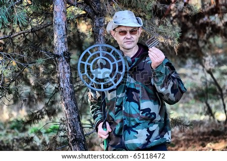 Military archeology. Man with metal detector and excavated German cartridges 7.92 mm caliber on the battlefield of WW2.Ukraine