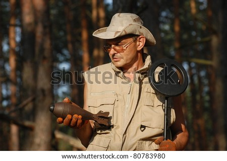 Military archeology. Man with metal detector and Soviet WWII 82-mm mortar-shell. Eastern Europe