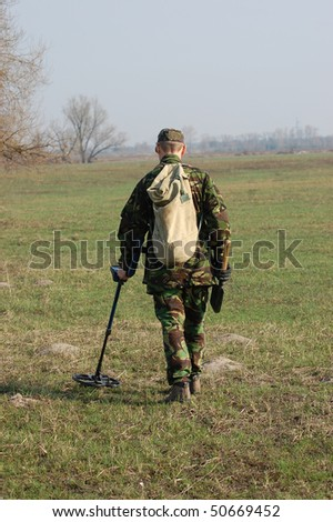 Military archeology. Man with metal detector on the battlefield of WW2.Ukraine - stock photo