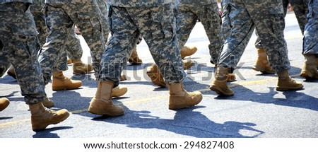 Military boots on the ground in a holiday parade outdoors.