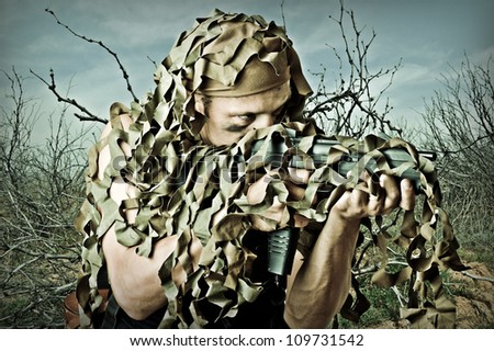 Military Camouflaged man aiming in forest from automatic