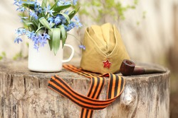 Military cap, ribbon, metallic cup and pipe, spring flowers close by on 9 of May card