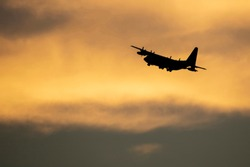 Military cargo jet departing against sunset clouds