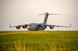 Military cargo plane parked on grassy meadow