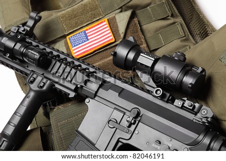Military concept. Green tactical body armor with U.S. stripe flag and M4A1 assault rifle close-up. Studio shot.