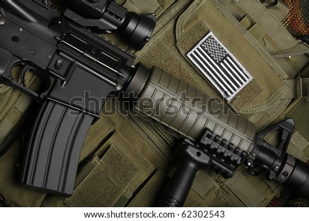 Military concept, still life. Tactical vest with U.S. battle flag and assault rifle with red-dot sight and tactical grip close-up. Studio shot.