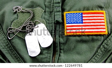 Military dog tags and American Flag patch on pilot flight suit