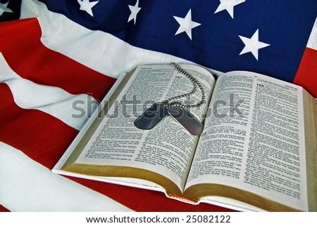 military dog tags and bible on flag