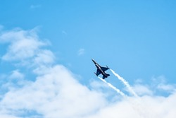 Military F16 fighter jet flying through the blue sky.